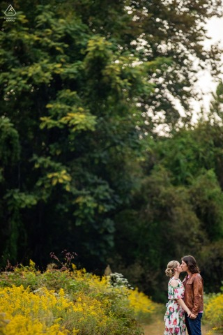 Frenchtown couple e-session in Hunterdon County, New Jersey with a kiss below the tall trees over the walking trail