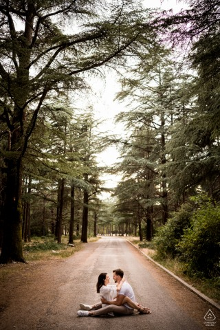 Luberon couple e-shoot sitting in the roadway below the tall forest trees