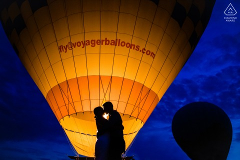 Cappadocia, Turkey couple engagement shoot silhouetted against a colorful balloon and a dark sky