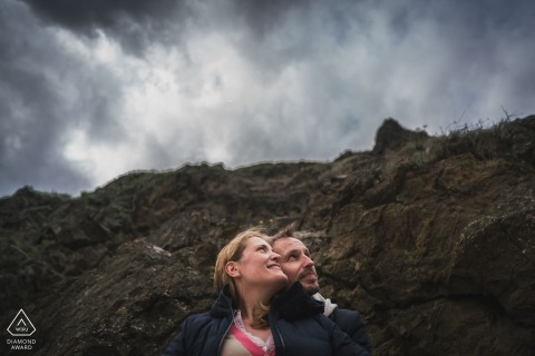Planguenoual, France couple e-session with lovers looking to the clouds in the sky above the hills