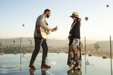 Cappadocia couple e-shoot in Turkey on the glass overlook with an acoustic guitar and hot air balloons