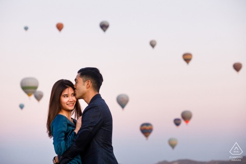 Cappadocia couple e-session in Turkey with a tender kiss below the colorful hot air balloons