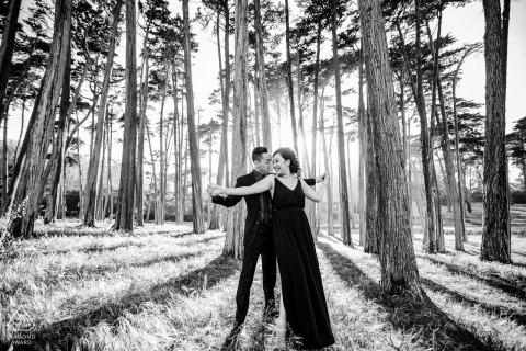 La pareja de Presidio of San Francisco e-shoot en BW con los árboles y un resplandor de luz del mediodía