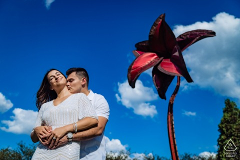 Grant Park couple e-session in Chicago under a sculpture of a red flower against a blue sky