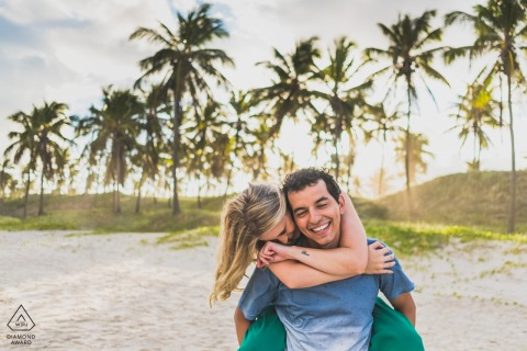 Maceió, Brazil couple e-session at the beach with a piggy back laughing hug on the sand