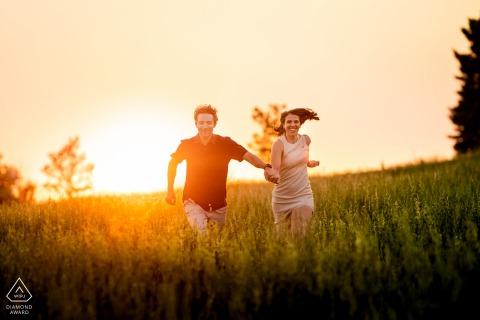 Denver-Paar läuft bei Sonnenuntergang während ihrer Verlobungssitzung am Blackmer Lake durch ein offenes Feld