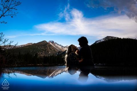 Braut und Bräutigam von Estes Park, die sich für ein Verlobungsbild am Bear Lake im RMNP . posieren