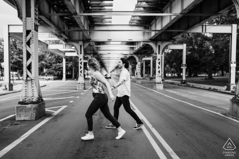 Chicago bride and groom to be, running under a bridge during a pre-wedding picture session in black and white