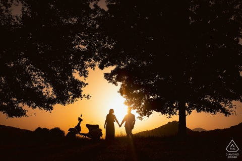 Alvito couple posturing for an engagement image at sunset with a moped in Frosinone