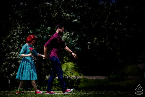 Bucharest bride and groom to be, modeling for a pre-wedding picture as they walk in the park with her flowers