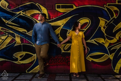 San Jose, CR bride and groom to be, posturing for an engagement image at Paseo Los Damas while holding hands posing at a graffiti Wall