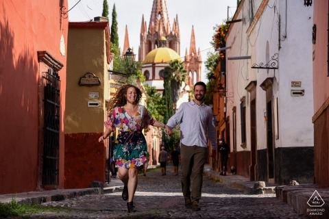 San Miguel de Allende bride and groom to be, running for a pre-wedding picture at Calle Aldama with the direct view it has towards the Parish