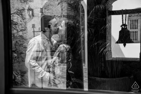 San Miguel de Allende bride and groom to be, posing for a pre-wedding engagement photo shoot at the Parque Juarez in Mexico with several reflections used between glass windows, the bell in the background gives it the romantic musical touch