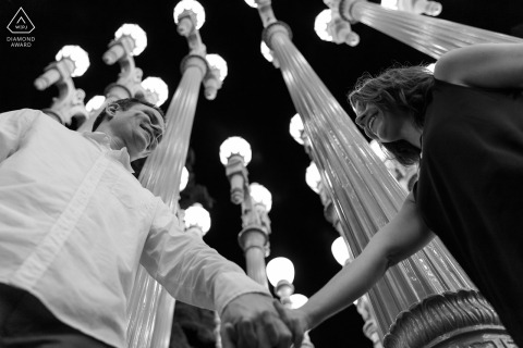 Los Angeles bride and groom to be, posing for a pre-wedding engagement photo shoot at the LA County Museum of Art as they hold hands below at a street light installation