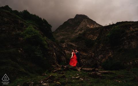Les futurs mariés des Pyrénées se posent pour une image de fiançailles du Lac d'Estaing sur les montagnes avec une robe rouge
