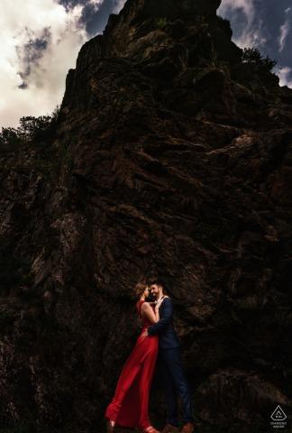 Lac d'Estaing futurs mariés, posant pour une séance photo de fiançailles avant le mariage dans les Pyrénées sur une falaise avec sa robe rouge