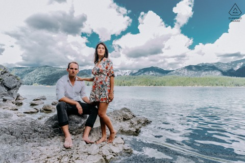 Munich bride and groom to be, posing for a pre-wedding engagement photo shoot by the water edge with clouds overhead