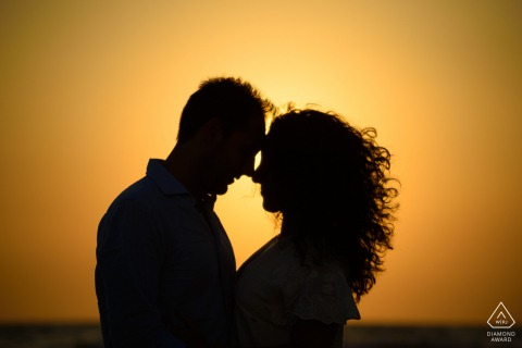 Paestum Beach bride and groom to be, posing for a pre-wedding engagement photo shoot at sunset on the beach forming a heart-shaped silhouette