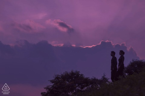 Shenzhen bride and groom to be, modeling for a pre-wedding picture in China against a purple sky with clouds
