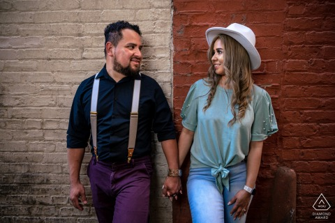 Knoxville bride and groom to be, posing for a Market Square pre-wedding engagement photo shoot in front of a painted wall in the alley