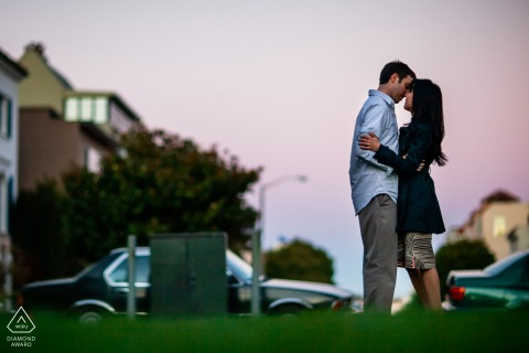 San Francisco bride and groom to be, modeling for a pre-wedding picture showing The lovers kissing in the city twilight