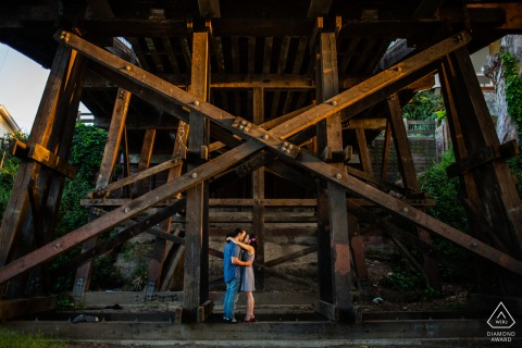 Santa Cruz bride and groom to be, posing for a pre-wedding engagement photo shoot of the couple hugging and kissing under the wooden railroad bridge