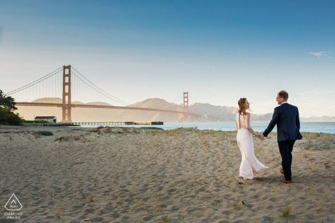 San Francisco bride and groom to be, posturing for a Bay Area engagement image of lovers happily strolling on the beach by the Golden Gate Bridge