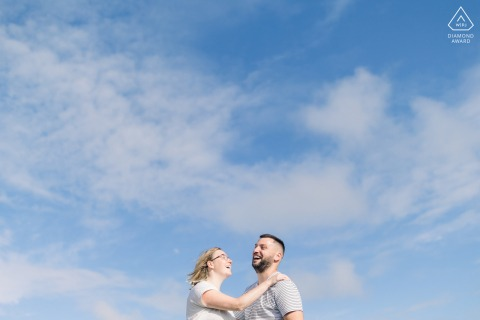 Vendee bride and groom to be, modeling for a Les Sables d'Olonne pre-wedding picture of a couple laughing on the seaside in front of the sky as a background