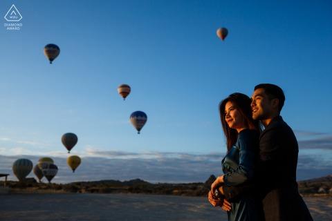 Cappadocia futuri sposi, in posa per un'immagine di fidanzamento con una bella luce che colpisce la coppia con mongolfiere in lontananza