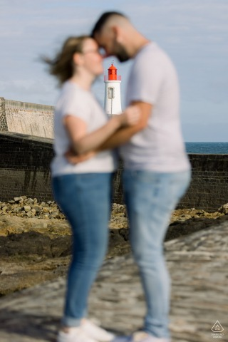 Vendee bride and groom to be, modeling for a pre-wedding picture in Les Sables d'Olonne with a lighthouse behind the couple
