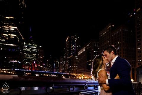 Les futurs mariés de Chicago se posent pour une image de fiançailles avec une prise de vue nocturne sur le pont de La Salle St en utilisant le réverbère derrière moi pour les éclairer, ainsi qu'un flash derrière eux pour l'éclairage de la jante