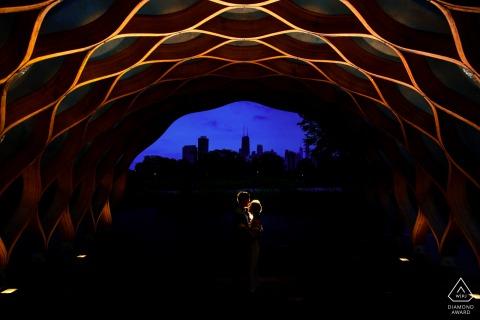 Les futurs mariés de Chicago, posant pour une séance photo de fiançailles avant le mariage à Lincoln Park avec une lumière à vitesse unique derrière eux gélifiés avec un CTO et une grille et l'ont tiré directement dans les airs ont laissé tomber l'exposition de sorte que l'ambiance soit sombre