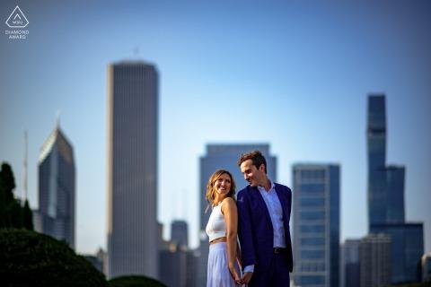 Les futurs mariés de Chicago, dos à dos pour une séance photo de fiançailles avant le mariage à Grant Park dans l'Illinois avec une compression complète et prise d'un angle inférieur pour comprimer les tours en arrière-plan pour montrer l'emplacement