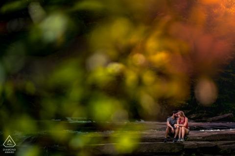 Les futurs mariés de Caroline du Nord, assis pour une séance de fiançailles avant le mariage à Asheville du couple assis le long d'une cascade après une proposition surprise où elle a dit oui