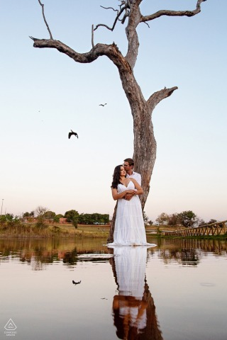 Jatai bride and groom to be, holding each other under a tree for a Pontal do Urutau pre-wedding engagement photo shoot