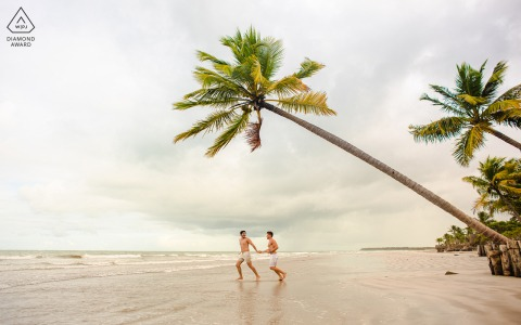 Les futurs mariés de Maceio se posent pour une image de fiançailles du couple courant sur le sable de la plage, et au-dessus d'eux se trouve un cocotier