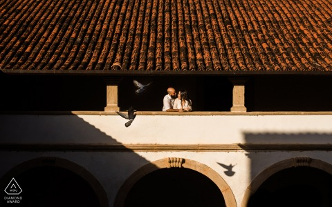 Alagoas bride and groom to be, posing for a Marechal Deodoro pre-wedding engagement photo shoot of the couple in a church, and holding each other while birds fly around them