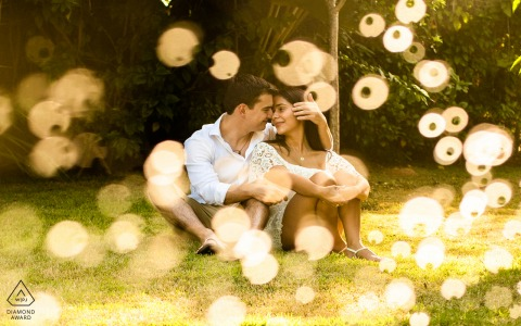 Alagoas bride and groom to be, sitting for a Sao Miguel dos Milagres pre-wedding engagement session of the couple sitting on the grass, and the sunlight has a different effect on the drops of water