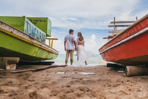 Maceio bride and groom to be, posturing for an engagement image in front of the sea between a green and red boat