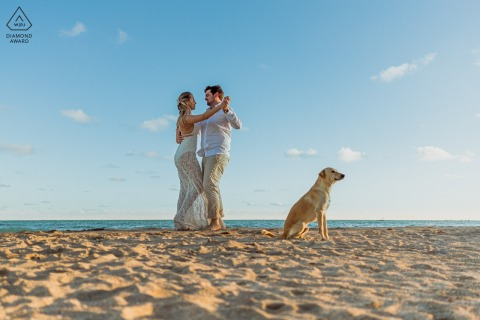 Maragogi bride and groom to be, modeling for a pre-wedding picture as the couple dance on the beach with a dog watching