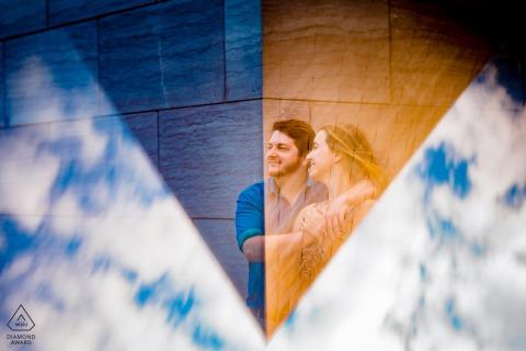 DC aanstaande bruid en bruidegom, modellerend voor een pre-huwelijksfoto in de National Gallery of Art in het East Building terwijl het paar omhelst, naar links kijkend, op de hoek van het gebouw, ingelijst in een driehoekige reflectie