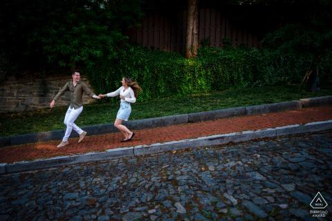 Aanstaande bruid en bruidegom in Georgetown, poseren voor een fotoshoot voor pre-huwelijksverloving in DC terwijl het stel speels over een steile stenen stoep rent