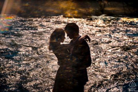 VA aanstaande bruid en bruidegom, poserend voor een fotoshoot in silhouet voorafgaand aan het huwelijk in Great Falls, het paar omhelst elkaar en een weerspiegeling van water vult hun silhouet in één enkele opname