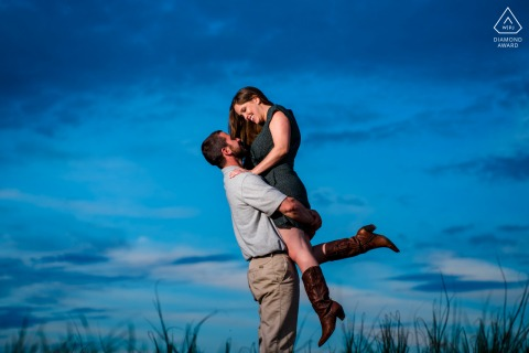 Maryland bride and groom to be, posturing for a family farm engagement image created as The groom-to-be lifts his fiance who is wearing cowboy boots up at dusk