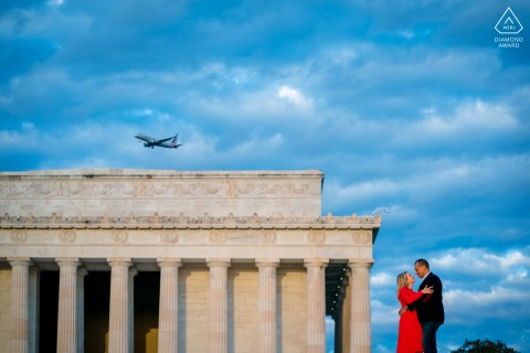 DC bride and groom to be, posing for a Lincoln Memorial pre-wedding engagement photo shoot as a plane flies overhead