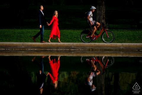 DC bride and groom to be, posturing for an engagement image at The Reflecting Pool as the couple walk along the pool, she's in a red dress, and a gentleman on a red capital bike share bike rides through the shot