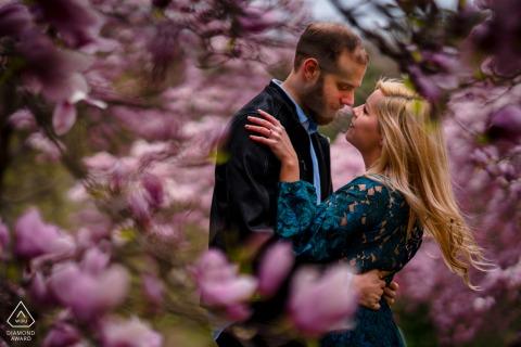 Aanstaande bruid en bruidegom in Washington DC poseren voor een pre-wedding verlovingsfotoshoot in het National Arboretum terwijl het paar elkaar omhelst op een winderige dag in de magnoliabomen
