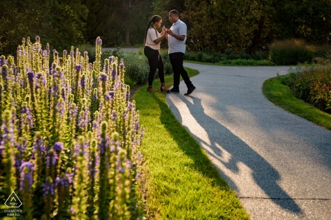 On location Montreal Botanical Garden engagement portrait shootwith the Couple dancing in the sunset light near flowers
