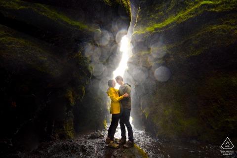Séance d'image avant le mariage d'un couple environnemental de l'Islande dans le canyon rocheux avec de la lumière venant à travers l'ouverture de la fissure