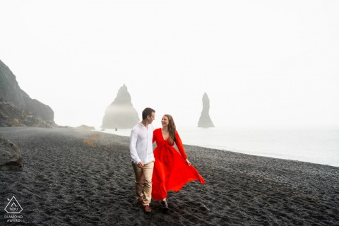 Sur place Islande black sands couple fiançailles portrait shoot dans une robe rouge au bord de l'eau